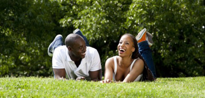 laughing black couple in grass
